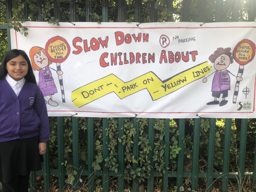 "Amelia, aged eight, with her eye catching banner saying: ""Slow down, children about"""