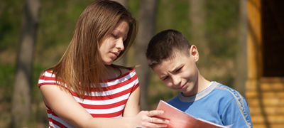 Boy reading to adult